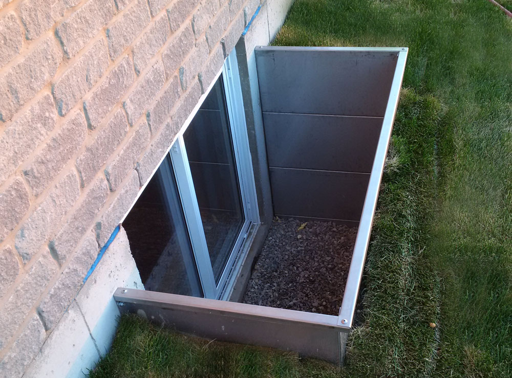 Modern Square Stainless Steel Egress Window Well new install with sod laid around it